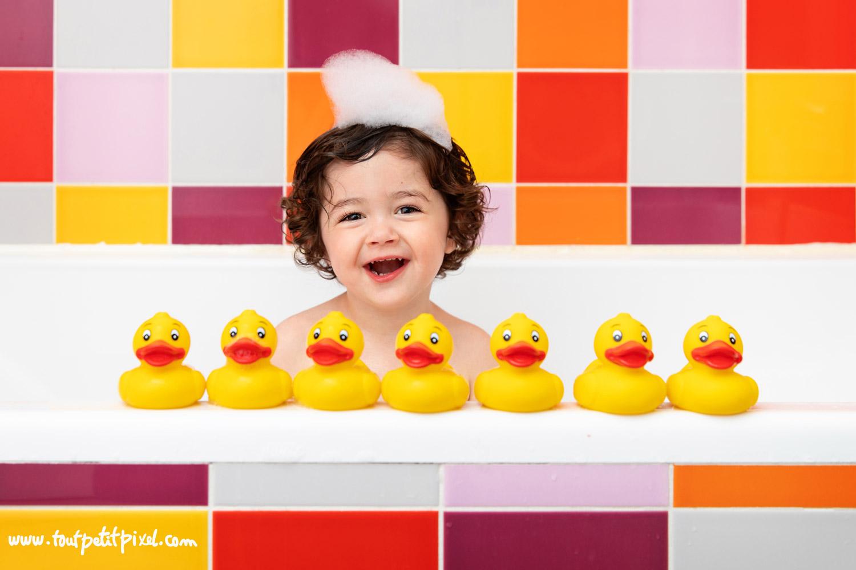Enfant qui rit en jouant avec des canards de bain par Tout Petit Pixel, photographe enfant lifestyle