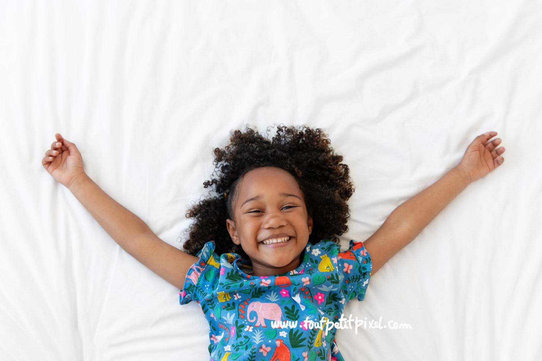 ortrait d'enfant qui sourit sur un lit blanc par Tout Petit Pixel, photographe enfant Marseille