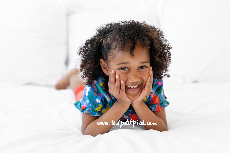 ortrait de petite fille qui sourit sur un lit blanc par Tout Petit Pixel, photographe enfant Marseille