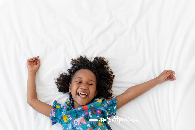 Portrait de petite fille qui rit sur un lit blanc par Tout Petit Pixel, photographe enfant Marseille