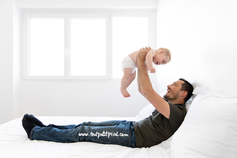 Papa et son bébé qui jouent sur un lit par Tout Petit Pixel, photographe bebe lifestyle à Marseille
