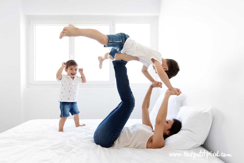 Maman et enfants qui font des acrobaties sur le lit par Tout Petit Pixel, photographe famille lifestyle
