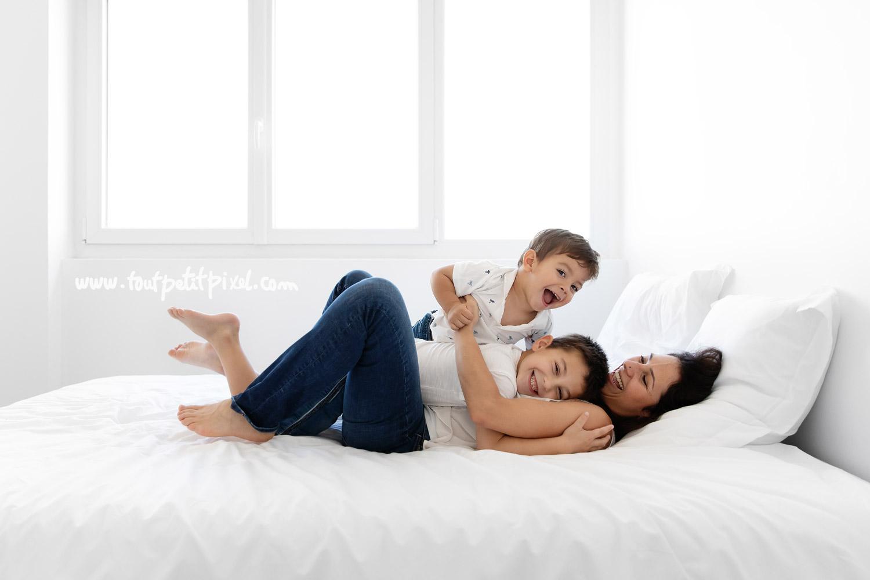 Maman et enfants qui jouent en riant sur le lit par Tout Petit Pixel, photographe famille lifestyle