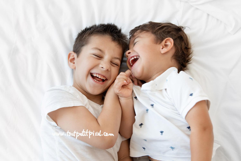 Deux jeunes enfants qui ont un fou rire sur le lit par Tout Petit Pixel, photographe famille lifestyle