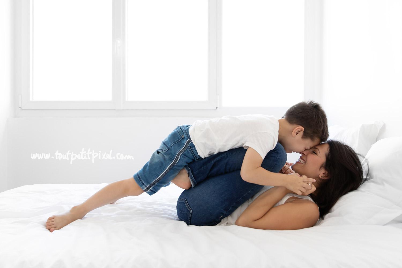 Maman et enfant qui jouent sur le lit nez à nez par Tout Petit Pixel, photographe famille lifestyle
