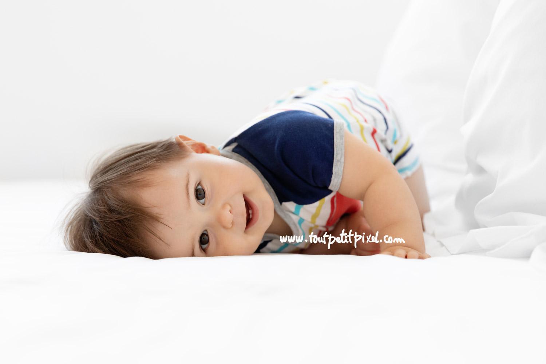 Bébé allongé sur un lit par Tout Petit Pixel, photographe bebe Marseille