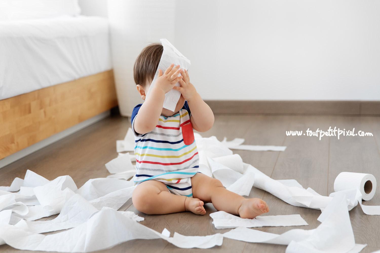 Bébé qui fait des bêtises avec du papier toilettes par Tout Petit Pixel, photographe bebe Marseille