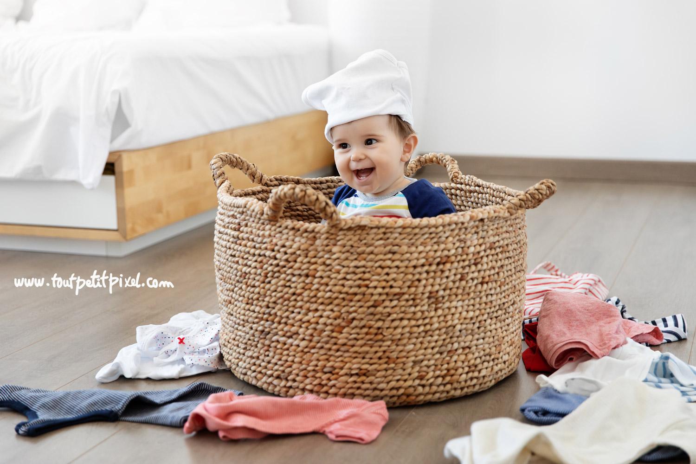 Bébé assis dans un panier à linge avec une culotte sur la tête par Tout Petit Pixel, photographe bebe Marseille