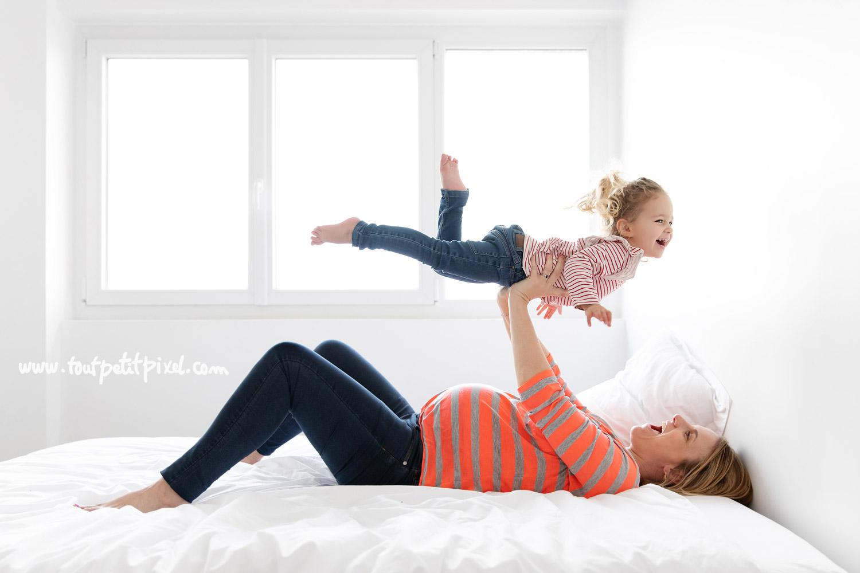 Femme enceinte qui joue avec sa petite fille sur un lit par Tout Petit Pixel, photographe enfant et famille Marseille