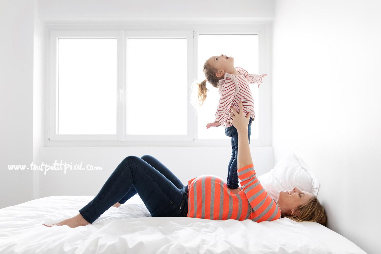 Femme enceinte qui joue avec son enfant sur un lit par Tout Petit Pixel, photographe enfant et famille Marseille