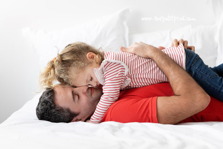 Un papa et sa petite fille qui font un calin sur un lit par Tout Petit Pixel, photographe enfant et famille Marseille
