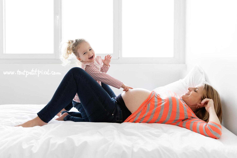 Petite fille qui touche le ventre rond de sa maman enceinte par Tout Petit Pixel, photographe enfant et famille Marseille