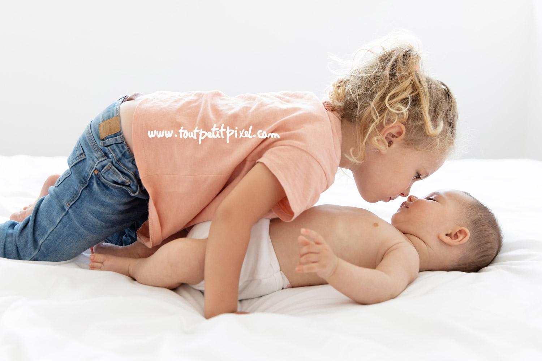 Bébé et grande soeur nez à nez sur un lit par Tout Petit Pixel, photographe enfant et famille Marseille