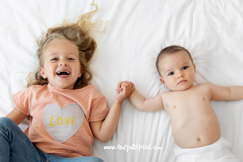 Bebe et grande soeur qui se tiennent la main sur un lit par Tout Petit Pixel, photographe enfant et famille Marseille