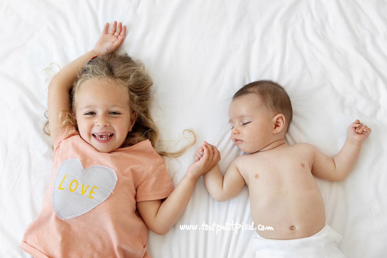 Petite fille souriante qui tient la main de son petit frere qui dort par Tout Petit Pixel, photographe bebe et famille Marseille