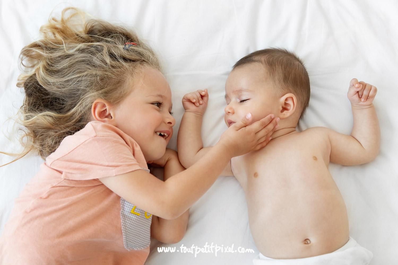 Petite fille souriante qui caresse la joue de son petit frere qui dort par Tout Petit Pixel, photographe bebe et famille Marseille