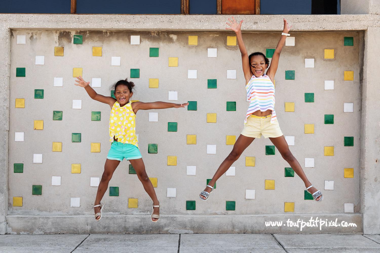 Petites filles qui sautent devant un mur coloré par Tout Petit Pixel, photographe enfant Marseille