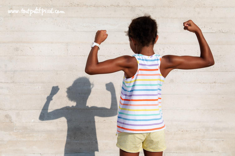 Petite fille qui montre ses muscles par Tout Petit Pixel, photographe enfant Marseille