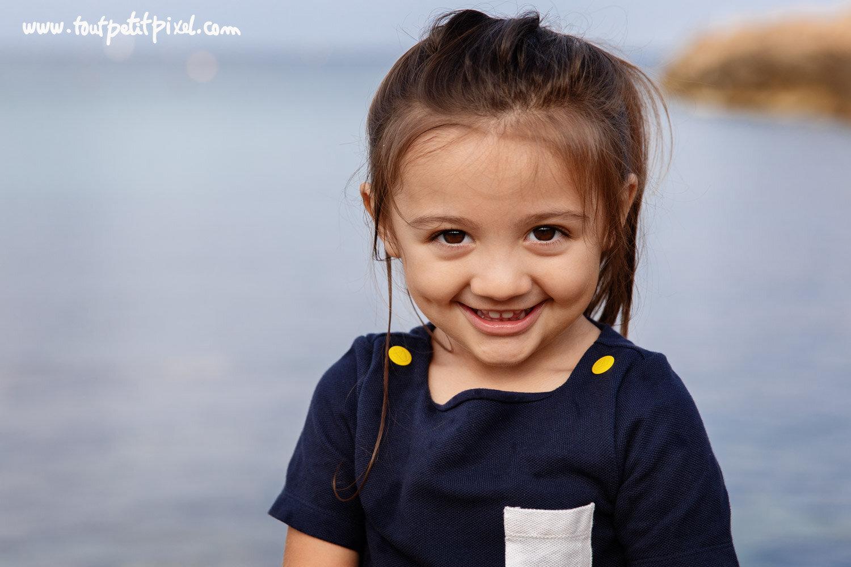 Portrait de petite fille qui sourit au bord de la mer par Tout Petit Pixel, photographe enfant et famille Marseille