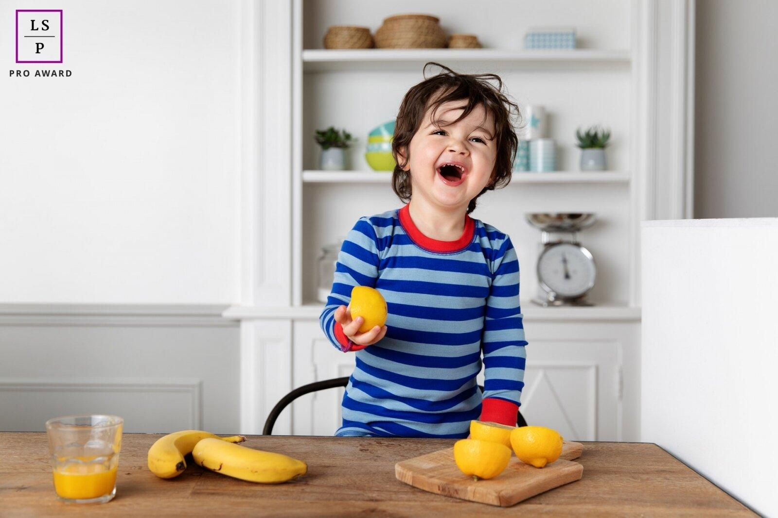 Enfant qui rit en mangeant des fruits par Tout Petit Pixel, photographe enfant lifestyle