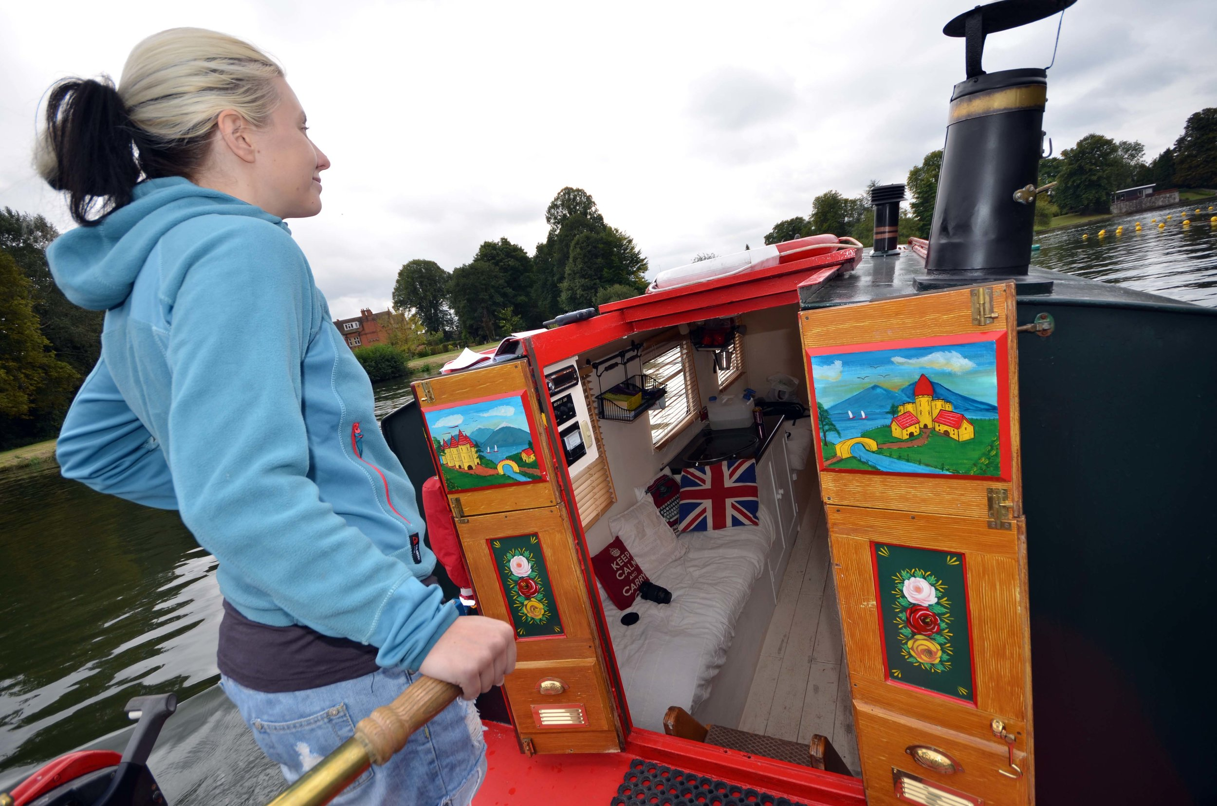 Phoebe at the tiller of her narrowboat taking things slowly in every sense. 📷by  Phoebe Smith