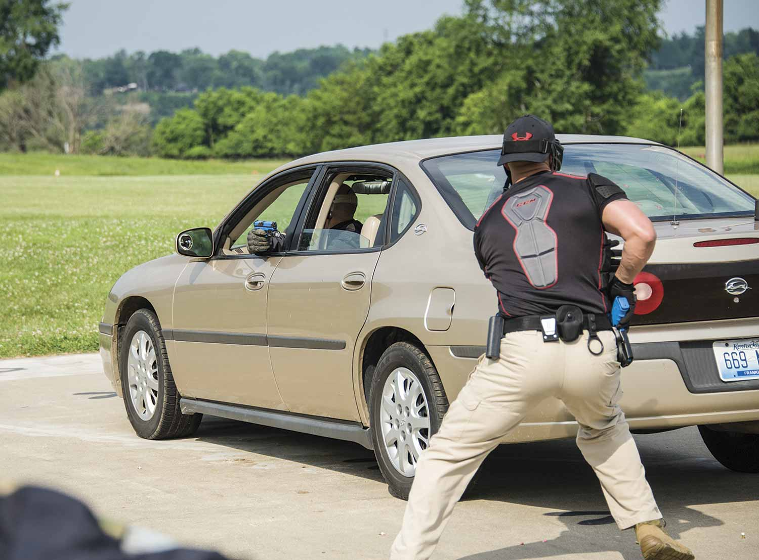 As officers in training approach a stopped vehicle, they are taught to keep their bodies close to the vehicle, making themselves a smaller target. (Photo by Jim Robertson)