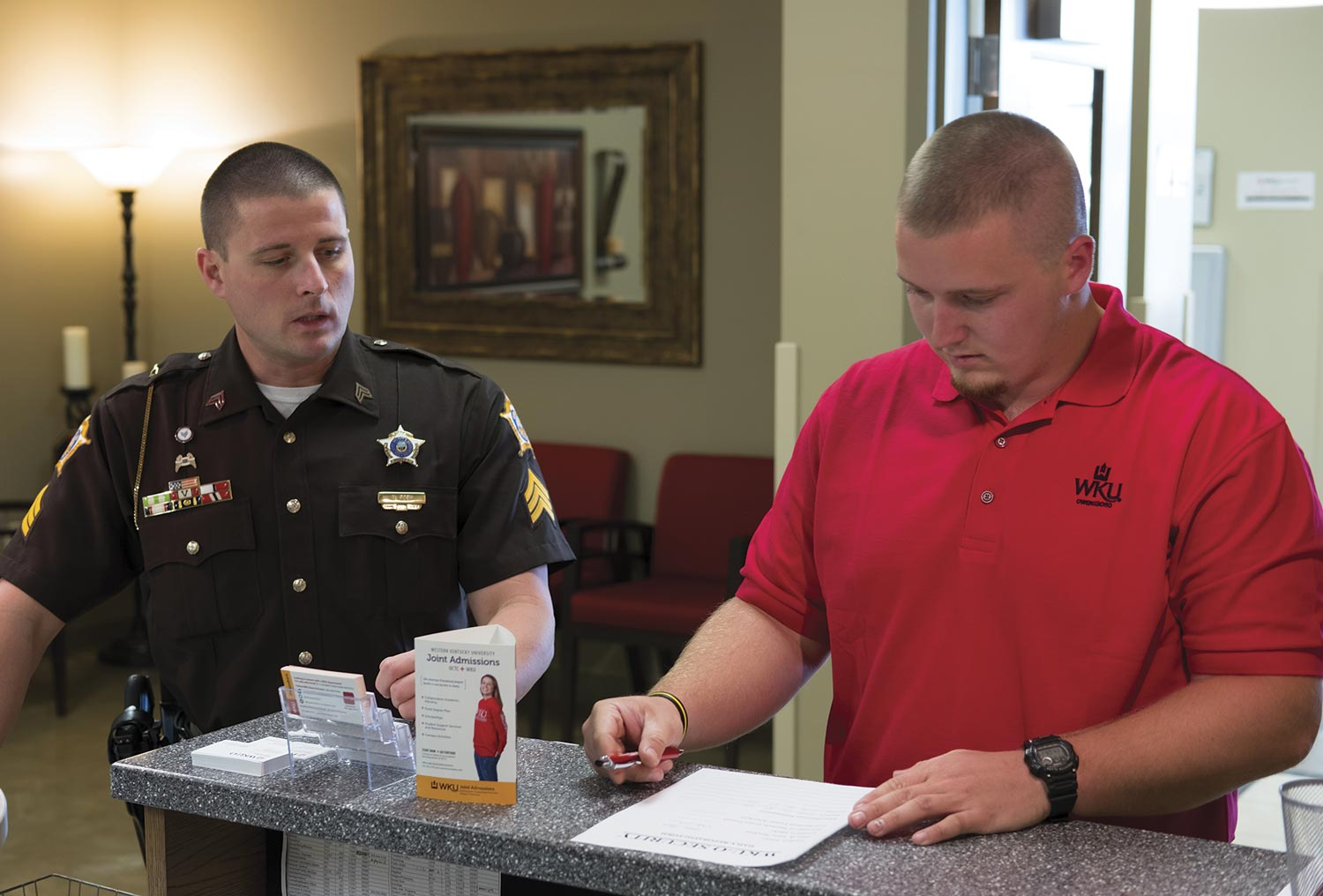 Colton Black, a sophomore at Owensboro Community and Technical College, prepares a duty report for Daviess County Sheriff's Sgt. Nick Roby, who oversees the Daviess County Sheriff's Office internship program. Patrolling the WKU-Owensboro campus gives the interns an experience of which they can take ownership. (Photo by Jim Robertson)