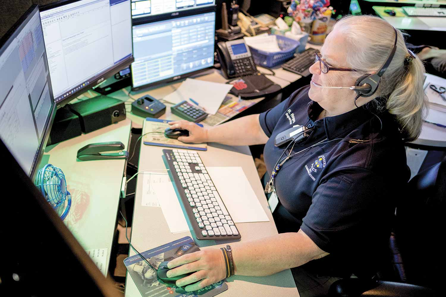 Winchester Police Communications Supervisor Rhonda Rogers answers an emergency call during an early-morning shift. Rogers said the Career Development Program helps transform dispatching from a run-of-the-mill job to a satisfying career. (Photo by Jim Robertson)