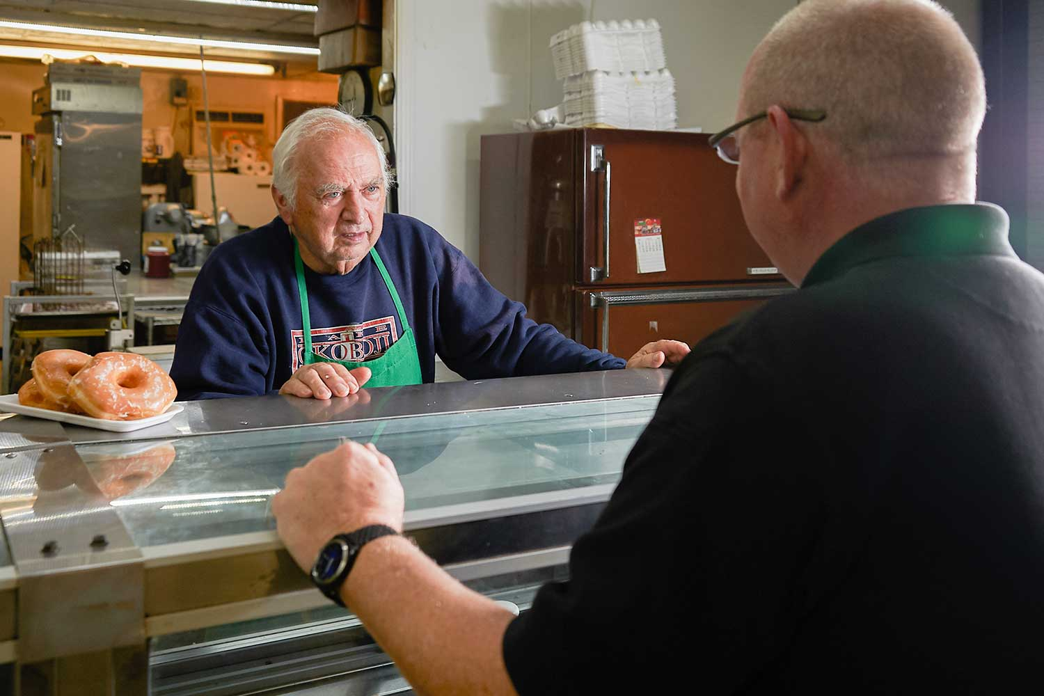 Wilmore Police Officer Sam Hensley stops by the city's lone grocery story, Fitch's IGA, to speak with owner Leonard Fitch.(Photo by Jim Robertson)