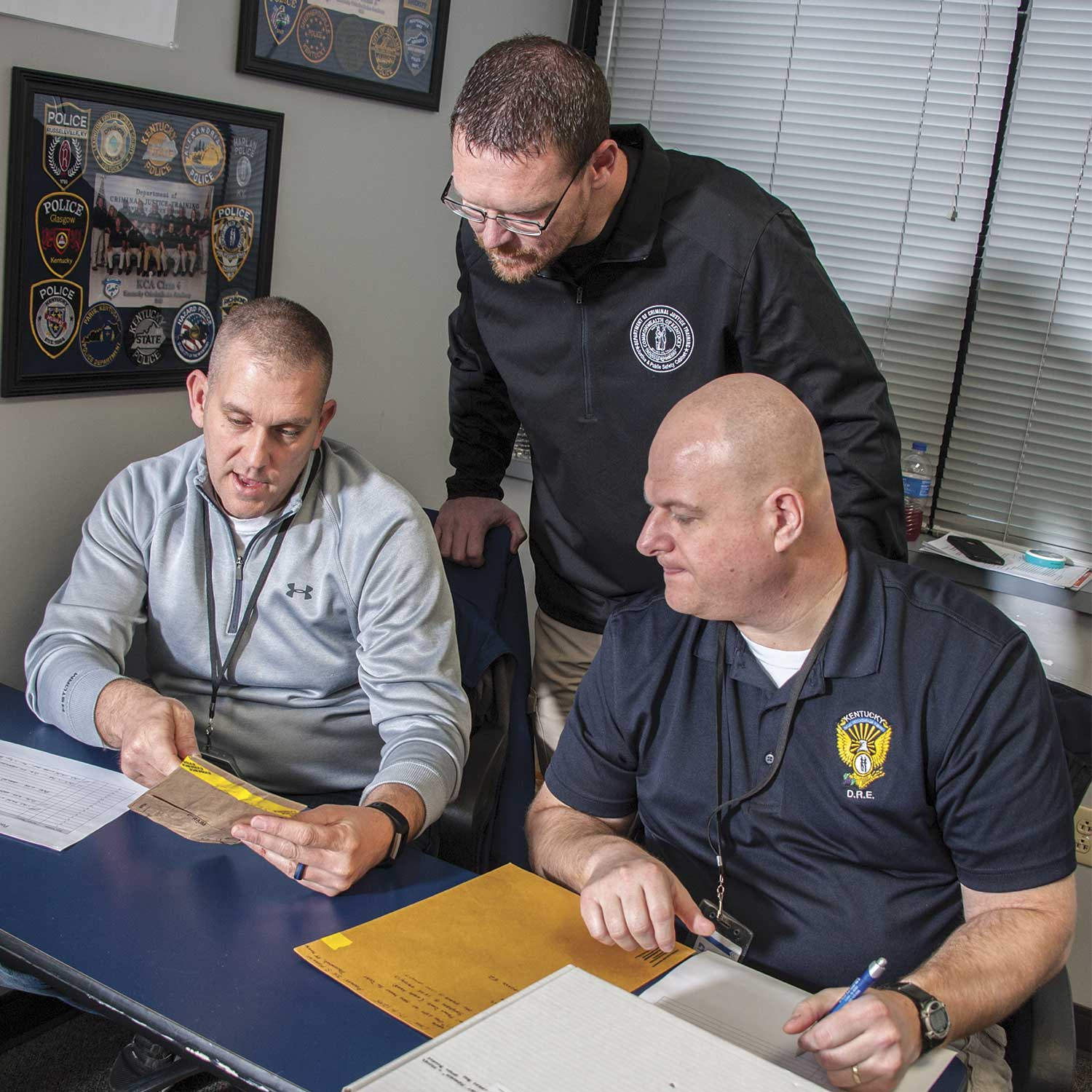 Department of Criminal Justice Training Instructor Shawn Moore answers a question from Kentucky State Police Sgt. Starling Hacker, left, and Williamsburg Police Sgt. Brandon White during the Property and Evidence Room Management course. (Photo by Jim Robertson)