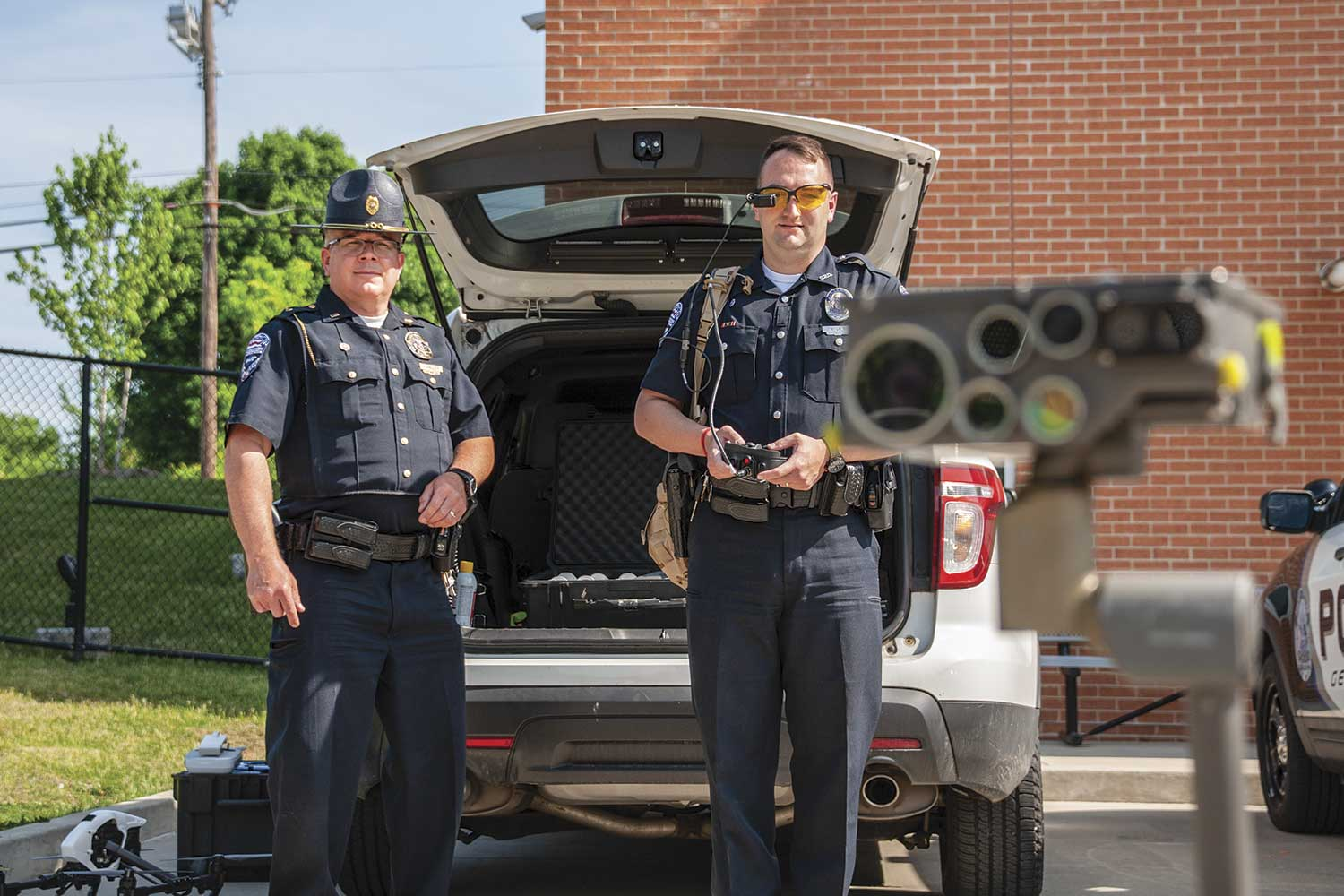 Georgetown Police Lt. Phil Halley, left, and Officer Mitch Lair demonstrate the department's robot, Johnny 5. The robot was obtained through military surplus at no cost to the agency. (Photo by Jim Robertson)