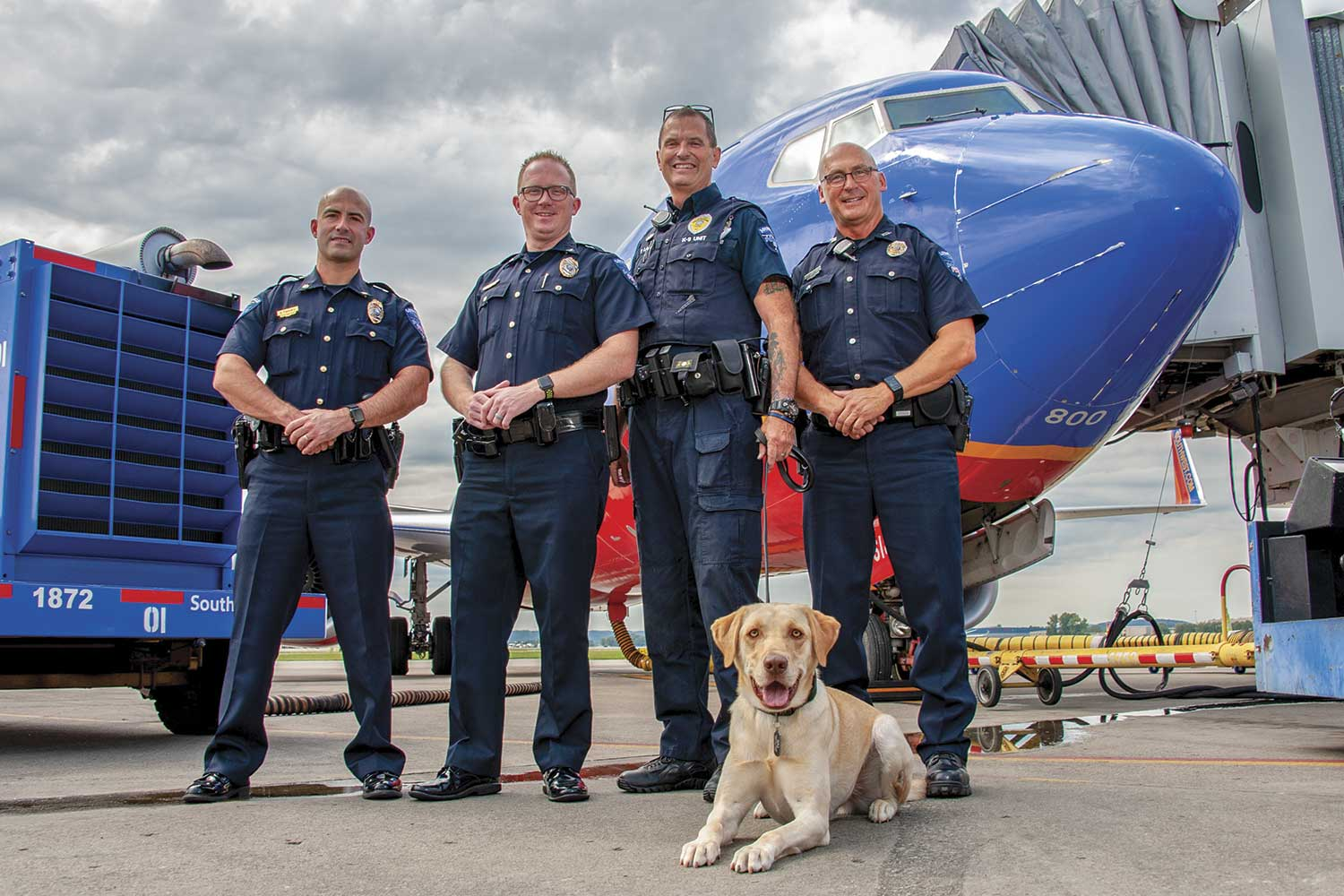 From left-to-right, Maj. Dustin Flannery, Chief Josh Ball, Officer Peter Lamb, K9 Raj and Officer Jeff Rogers pose in front of a Southwest Airlines plane on the tarmac at the Louisville International Airport. (Photo by Jim Robertson)