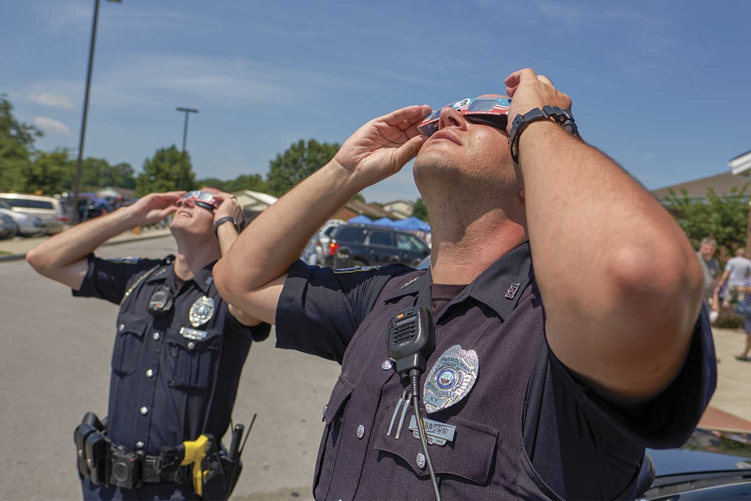 In August 2017, Russellville was a prime location for the solar eclipse. Officers Tate Piper, left, and Ryan Brown put on a pair of solar eclipse glasses to view the event. (Photo by Jim Robertson)