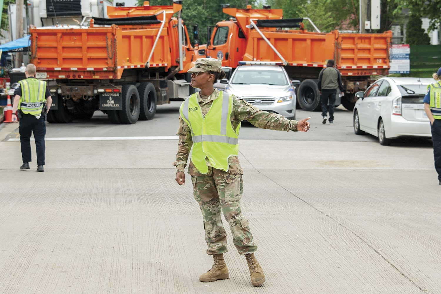An officer directs traffic in front of two large dump trucks. Dump trucks were first used at Kentucky Derby events in 2016, during the Pegasus Parade. According to Lt. Jill Hume, this was the first real security measure taken to prevent vehicle rammings like those going on around the world at that time. (Photo by Jim Robertson)