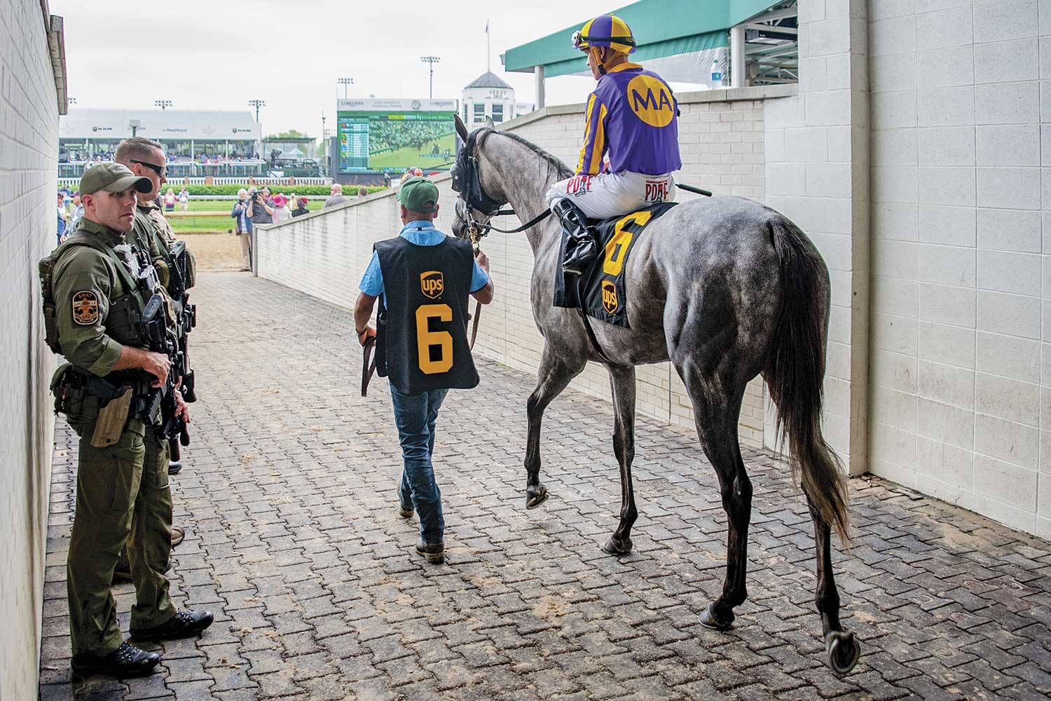 LMPD officers Matt Ernst, left, and Daniel Weedman check the Paddock Tunnel at Churchill Downs as jockeys and horses enter the track for an early race. (Photo by Jim Robertson)