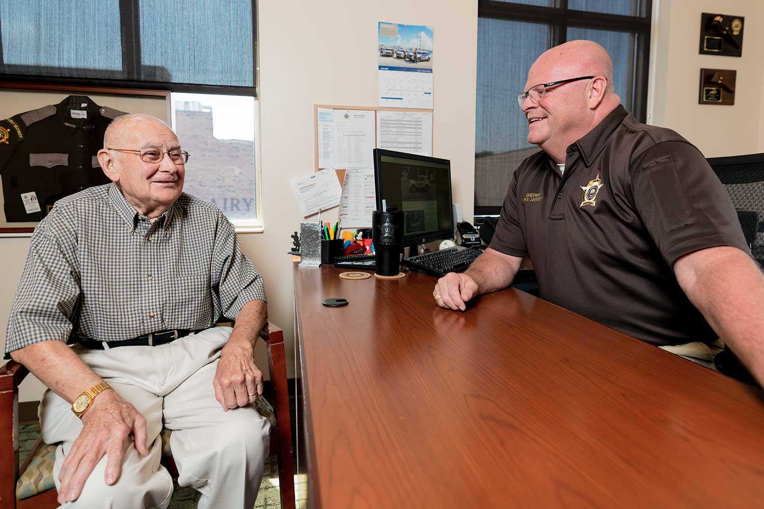Campbell County Sheriff Mike Jansen talks with retired deputy John Sayers after members of the sheriff's office presented him with a framed uniform. (Photo by Jim Robertson)