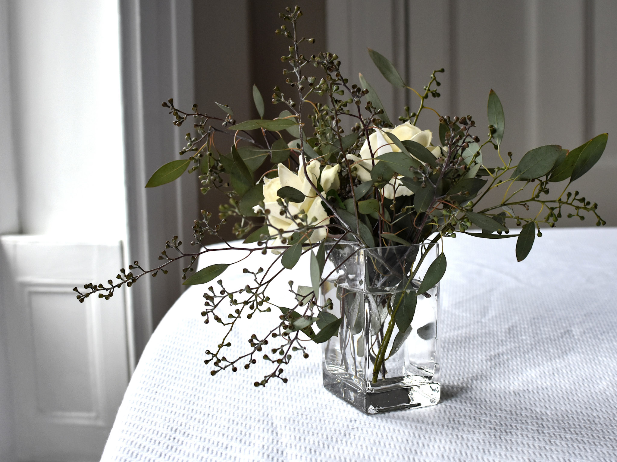 A simple arrangement of seeded eucalyptus and faux ivory roses will last all season if properly watered.
