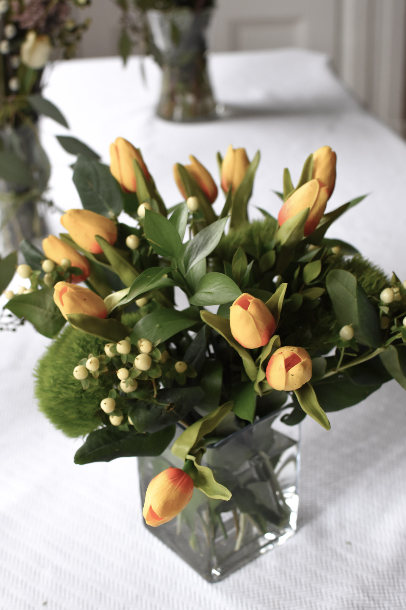Pretty faux tulips peek out of a bed of fresh green ruscus, ivory hypericum berries and poufy, moss-like dianthus flowers.