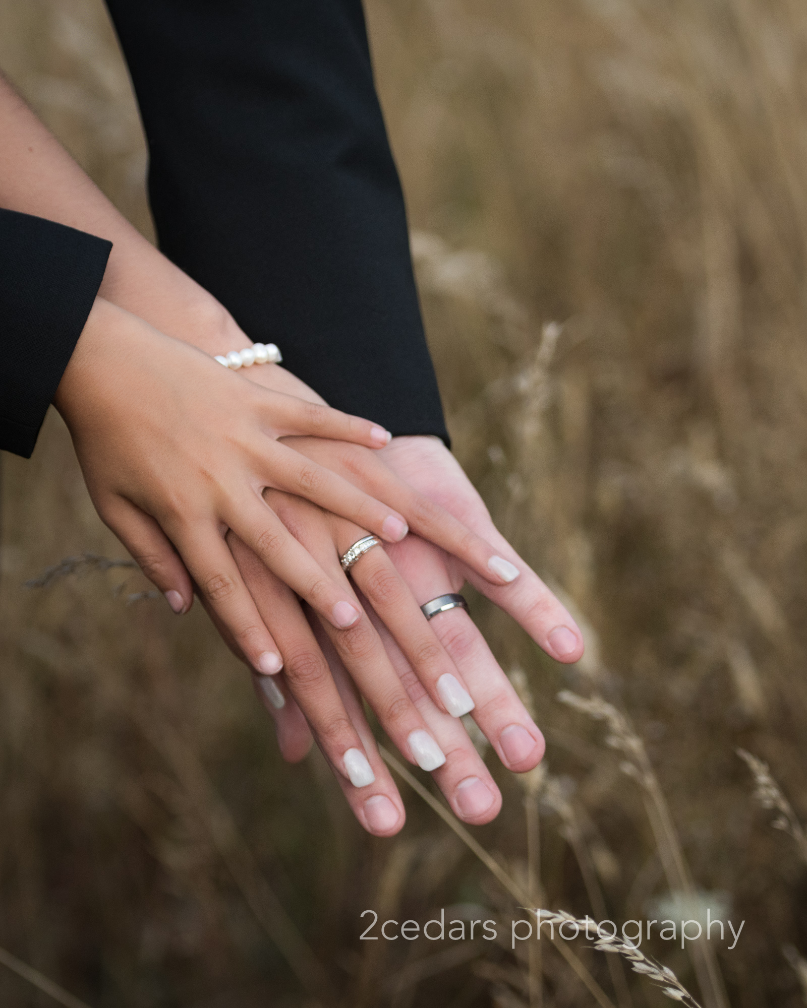 Bride and groom hands with child