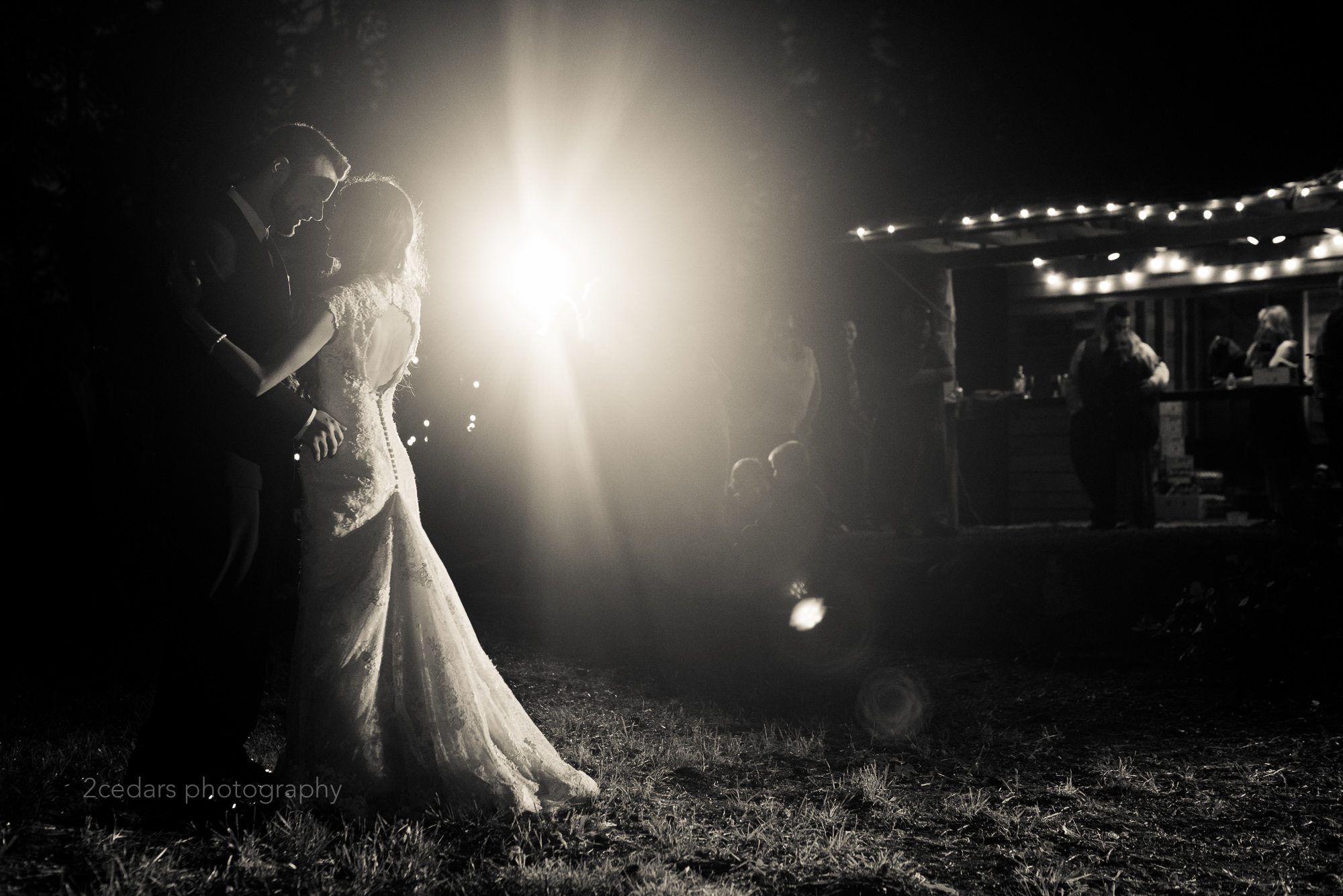 Bride and groom dancing at an outdoor Puget Sound wedding with backlight in black and white