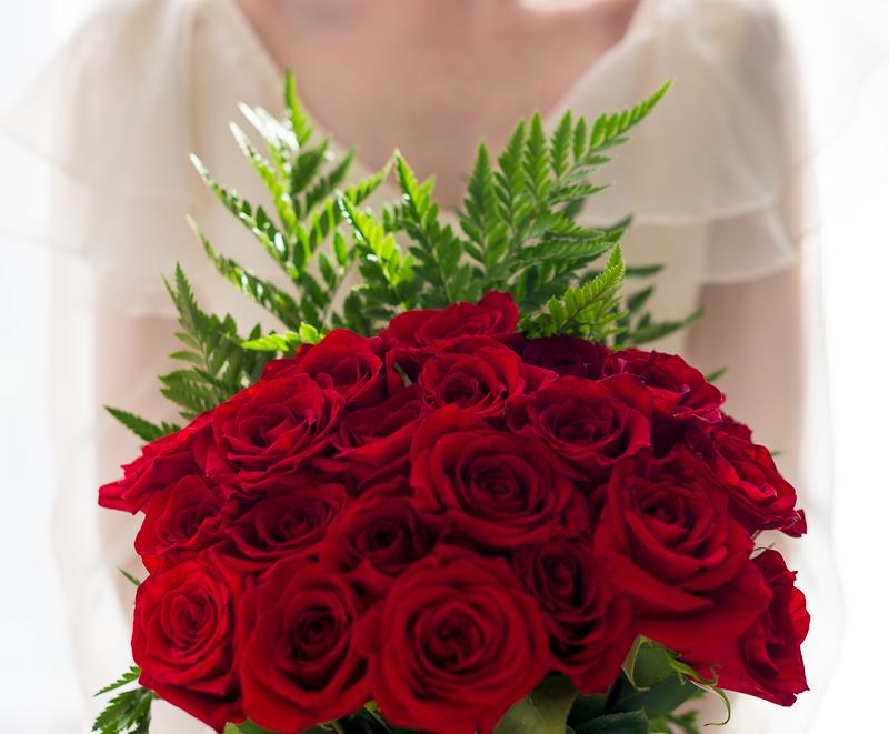 Bride red rose bouquet detail portrait in window light