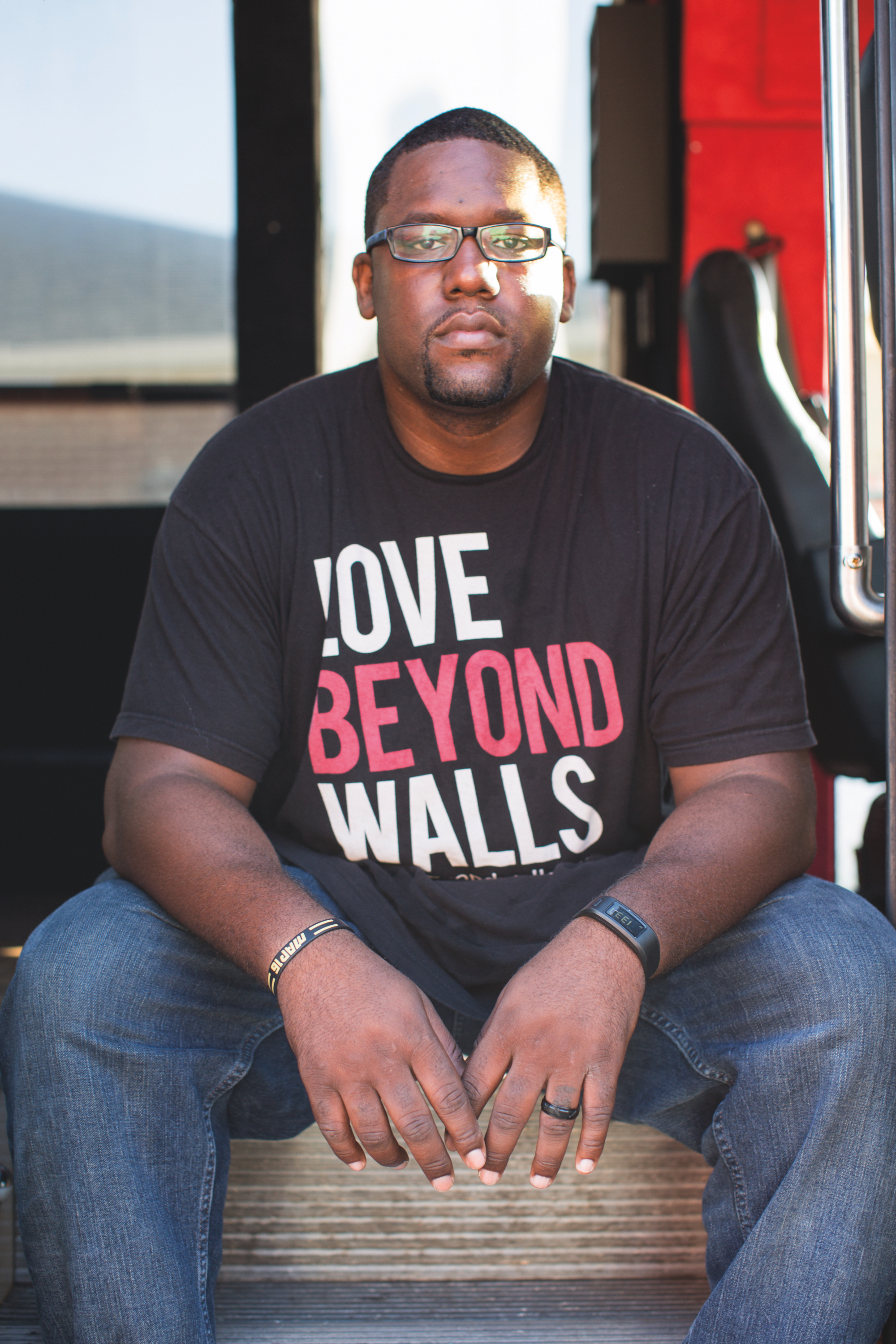 ABOVE: Terence Lester founder of Love Beyond Walls, sits on the steps of the orginization's mobile babershop.