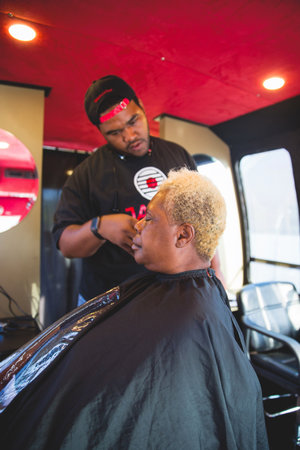 ABOVE: Javoris Brown gives Phyllis Williams a hair cut aboard the Love Beyond Walls bus — the same one Terence slept on top of to raise awareness about homelessness. The bus now travels the city, providing a welcome one-stop shop for hygiene for underserved people and those living on the streets.
