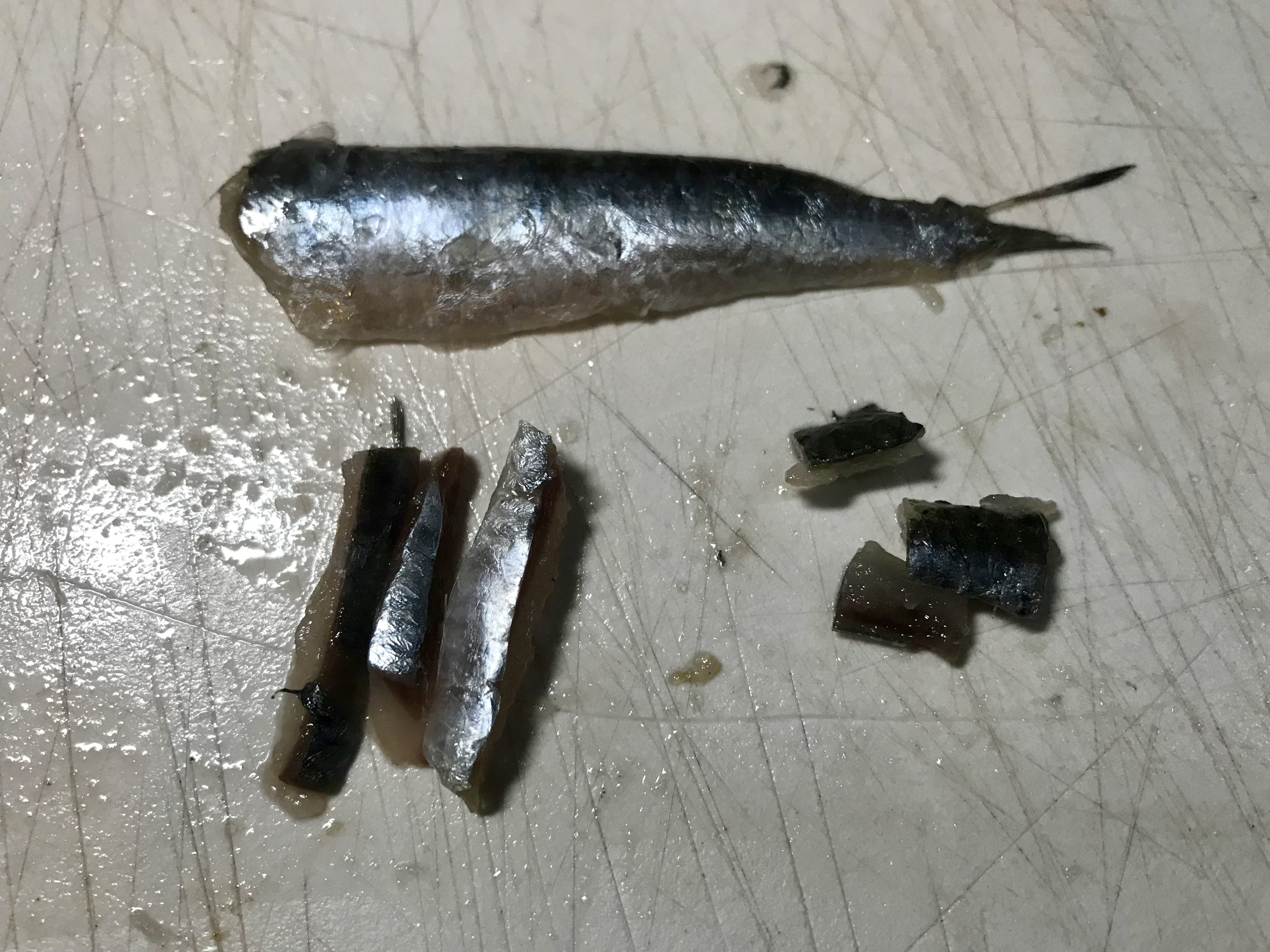 Fillet the anchovy and cut into appropriate sized pieces for your presentation.
