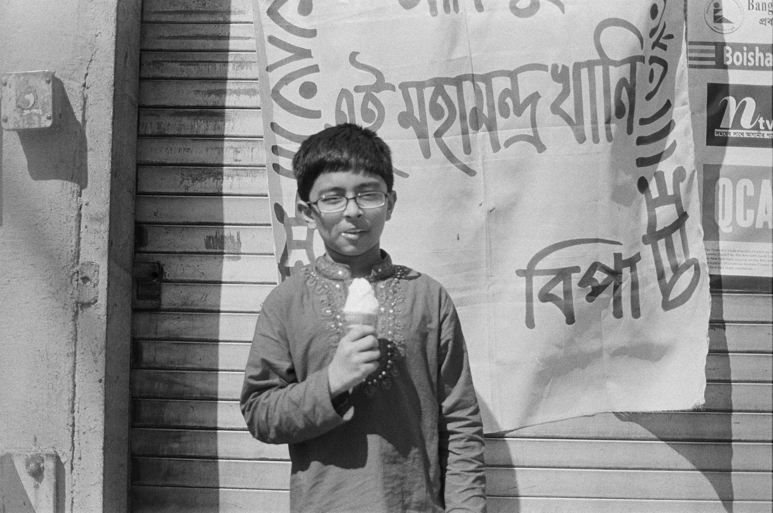 A young boy eats an ice cream cone during a Bengali day celebration.