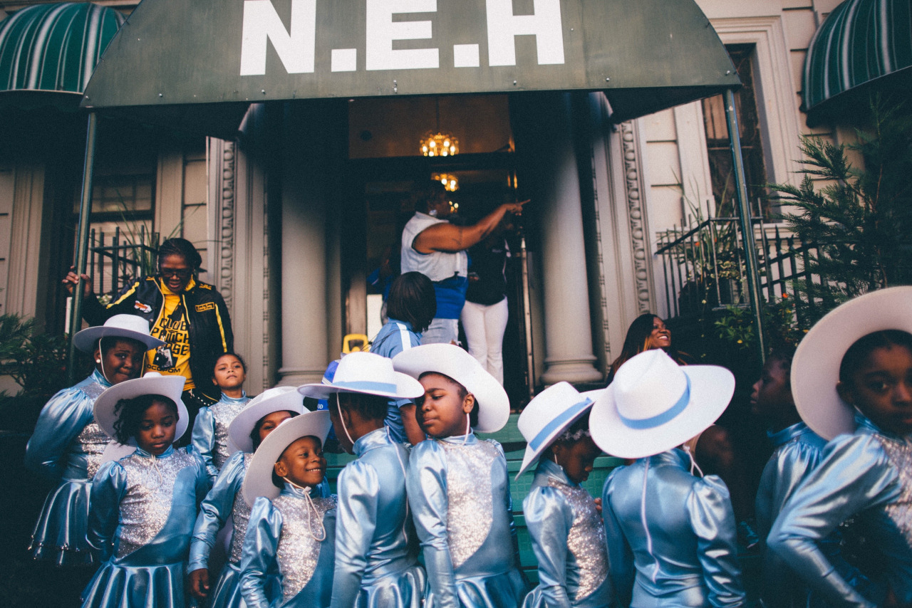 A dance troupe from New Jersey gathers before a performance in front of the New Ebony Hotel on West 112th Street. Harlem, New York.