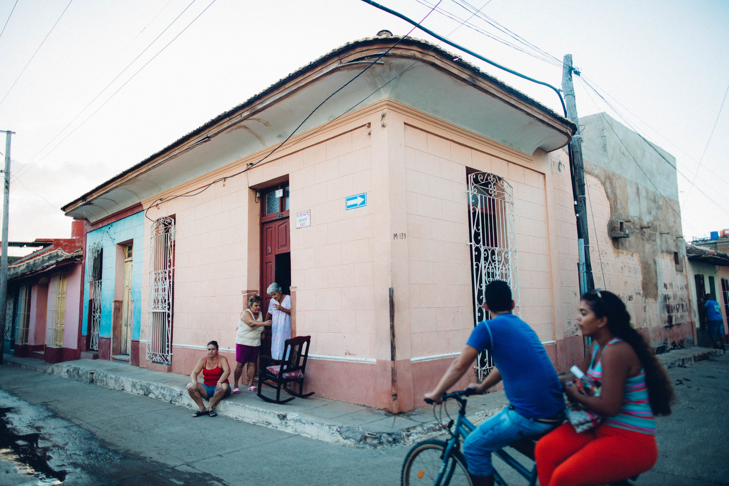 A daughter, a mother and a grandmother congregate outside their home in Trinidad as a young couple rides past on a bike. Trinidad, Cuba.