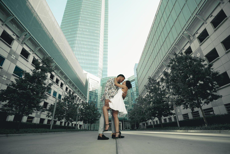 engagement-couple-dip-kiss-downtown-okc-buildings-trees.jpg