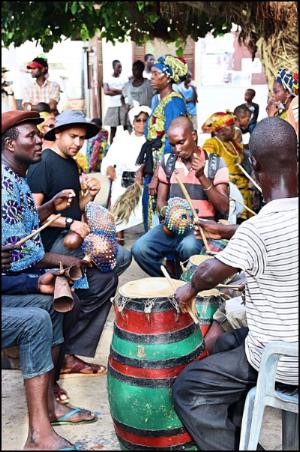 Derrick Spiva Jr. (in grey hat) playing axatse (shaker) with an Ewe music ensemble in Anyako, Ghana, July 2017.