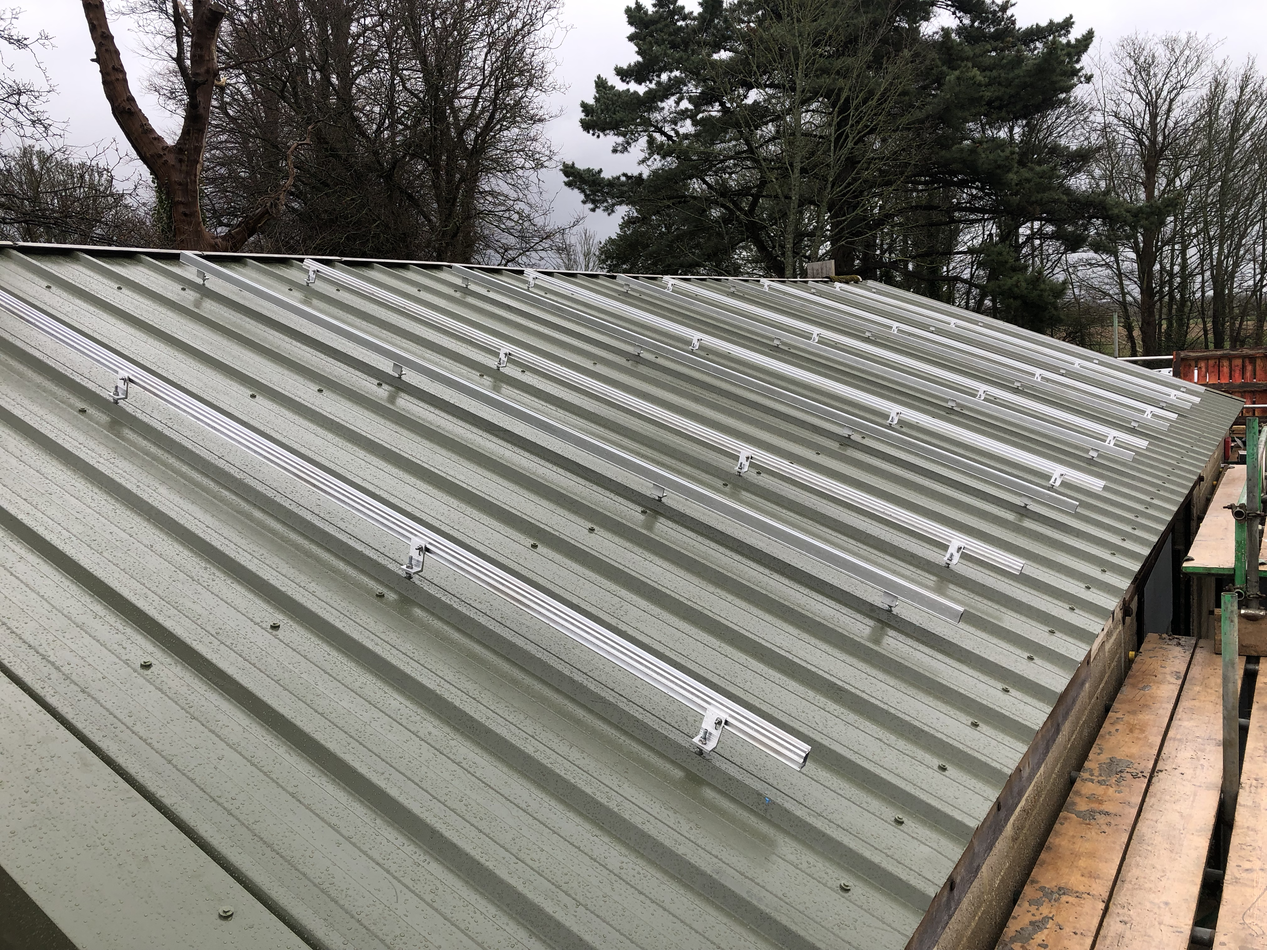 Installing the rails on a very wet and slippery roof. Harnesses and scaffolding fully used!!!!!